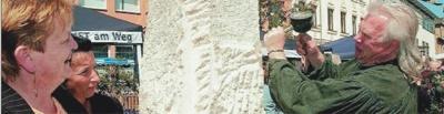 Jens Weber arbeitet aus einem groben Block Stein eine filigrane Tuchrolle mit Schiffchen heraus. Das